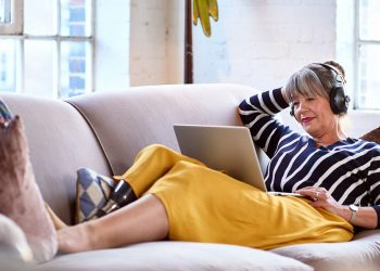 Woman in her 60s with prosthetic leg on sofa using laptop, relaxation, lifestyles, retirement